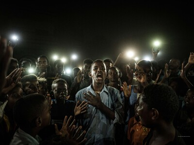 Yasuyoshi Chiba, Japan, Agence France-Presse - A young man, illuminated by mobile phones, recites protest poetry while demonstrators chant slogans calling for civilian rule, during a blackout in Khartoum, Sudan.